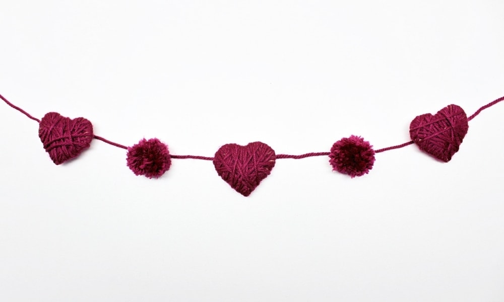 DIY Yarn Valentine's Day Garland with Yarn-Wrapped Hearts and Pom-Poms